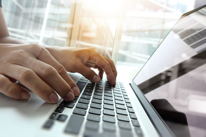 A person is working or typing on the laptop.