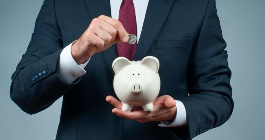 A man with a formal attire putting a coin in a piggy bank.